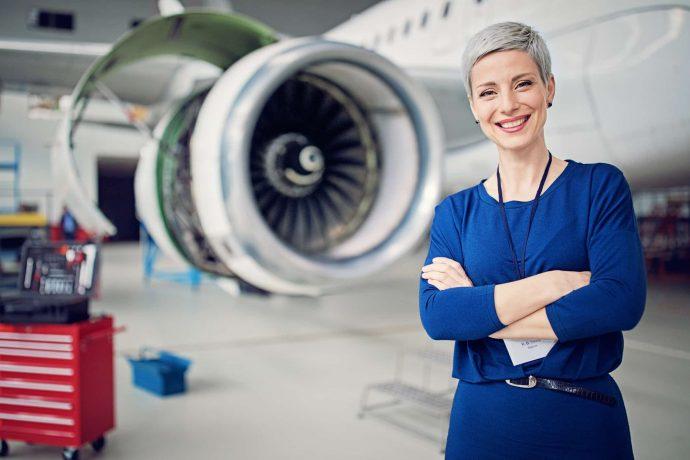 Ingenieurin steht vor einem Flugzeug