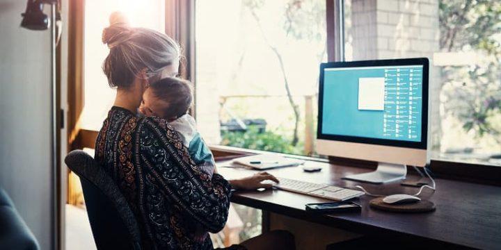 Junge Mutter mit Baby im Arm bei der Arbeit