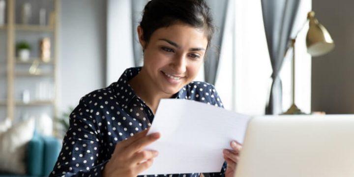 Junge Frau schaut sich Unterlagen zur Risikoprüfung an