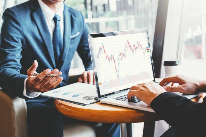 Geschäftsmänner unterhalten sich vor einem Laptop über Aktienkurse