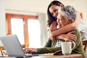 Ältere Dame sitzt am Laptop und wird von Tochter umarmt