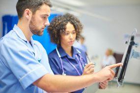 Eine Krankenschwester und ein Altenpfleger studieren ein Krankenblatt