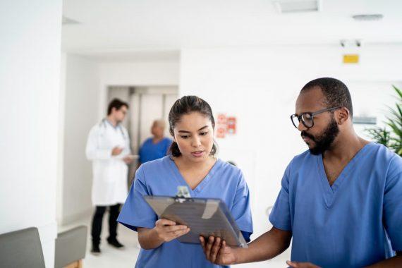 Zwei Krankenpfleger schauen gemeinsam auf ein Klemmbrett