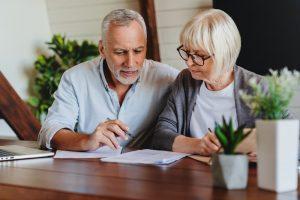 Fröhliches Ehepaar berechnet Auszahlung der Basisrente