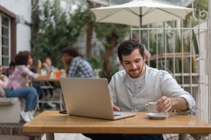Mann im Café informiert sich am Laptop zu Rentenversicherung
